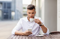 Man with smartphone drinking coffee at city cafe Stock Images
