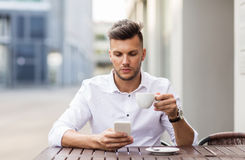 Man with smartphone drinking coffee at city cafe Royalty Free Stock Photo