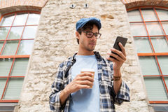 Man with smartphone drinking coffee on city street Royalty Free Stock Images