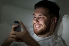 Man with smartphone and earphones in bed at night Royalty Free Stock Photos