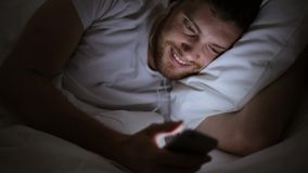 Man with smartphone and earphones in bed at night stock footage