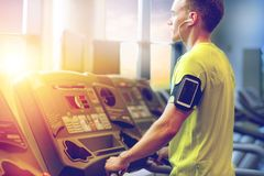 Man with smartphone exercising on treadmill in gym. Sport, fitness, lifestyle, technology and people concept - man with smartphone and earphones exercising on Royalty Free Stock Photos