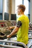 Man with smartphone exercising on treadmill in gym Stock Image