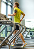 Man with smartphone exercising on treadmill in gym Stock Photography