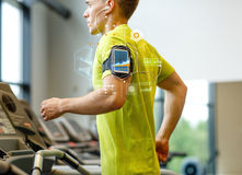 Man with smartphone exercising on treadmill in gym. Sport, fitness, lifestyle, technology and people concept - man with smartphone and earphones exercising on Stock Images