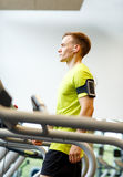 Man with smartphone exercising on treadmill in gym Royalty Free Stock Photos