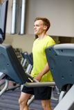 Man with smartphone exercising on treadmill in gym Royalty Free Stock Images