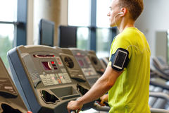 Man with smartphone exercising on treadmill in gym Stock Images