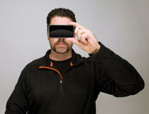 Man with smartphone by face. Thirty something man hiding his eyes behind a smartphone or iphone as in anonymity concept Royalty Free Stock Images
