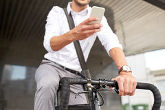 Man with smartphone and fixed gear bike on street. Business, people, communication, technology and lifestyle - man texting on smartphone with fixed gear bike on Royalty Free Stock Photos