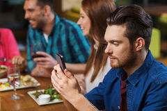 Man with smartphone and friends at restaurant Stock Photography