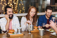 Man with smartphone and friends at restaurant Royalty Free Stock Photography