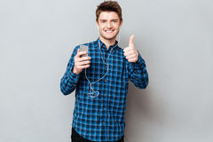 Man with smartphone and headphones showing thumbs up. Young man listening music with smartphone and headphones and showing thumbs up stock images