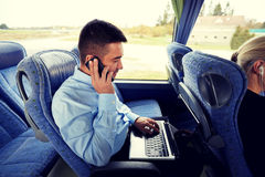 Man with smartphone and laptop in travel bus Stock Photo