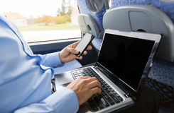 Man with smartphone and laptop in travel bus stock photography