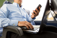 Man with smartphone and laptop in travel bus Royalty Free Stock Images