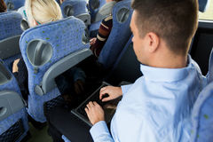 Man with smartphone and laptop in travel bus Stock Images