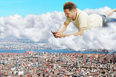 A man with smartphone laying on clouds above the megapolis city Royalty Free Stock Image