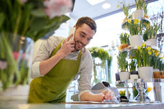 Man with smartphone making notes at flower shop Royalty Free Stock Image