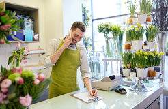 Man with smartphone making notes at flower shop Stock Image