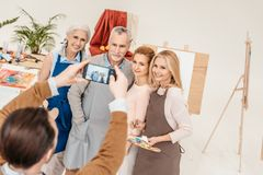 Man with smartphone photographing senior and mature students at art. Class stock photos