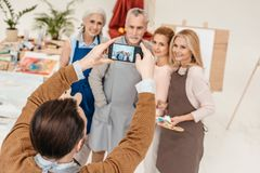 Man with smartphone photographing senior students at art. Class stock images