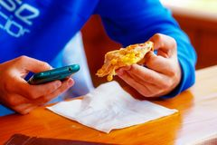 Man with smartphone and pizza in hands. royalty free stock photo