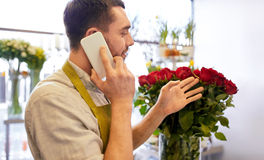 Man with smartphone and red roses at flower shop Royalty Free Stock Photos