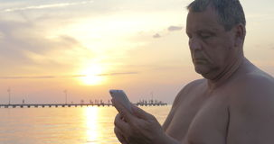 Man with Smartphone by the Sea at Sunset stock footage