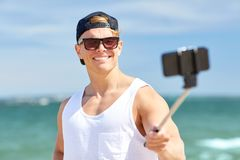 Man with smartphone selfie stick on summer beach. Summer holidays and people concept - happy smiling young man with smartphone selfie stick taking picture on Stock Images