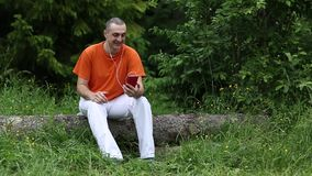 Man with smartphone sits on a fallen tree in the forest stock video