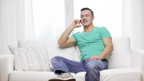 Man with smartphone sitting on couch at home stock video