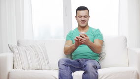 Man with smartphone sitting on couch at home stock video footage