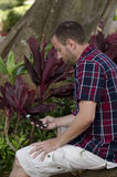 Man on a smartphone. Man sitting and utilizing a smartphone Stock Images