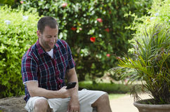 Man on a smartphone. Man sitting and utilizing a smartphone Royalty Free Stock Image