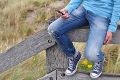 Man with smartphone. Man sitting on a wooden balustrade at the beach checking his smartphone Royalty Free Stock Photography