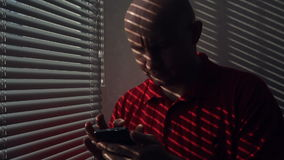 Man with a smartphone standing at the window with blinds stock video