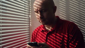 Man with a smartphone standing at the window with blinds stock footage