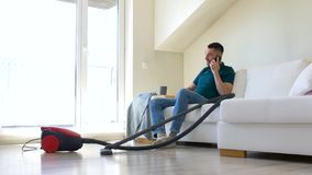 Man with smartphone and vacuum cleaner at home. Cleaning, household and technology concept - happy man with smartphone and vacuum cleaner at home stock footage