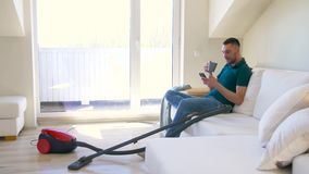 Man with smartphone and vacuum cleaner at home. Cleaning, household and technology concept - happy man with smartphone and vacuum cleaner drinking tea at home stock video