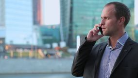 Man on smartphone - young business man talking on smart phone. Casual urban professional businessman using mobile cell. Phone stock video footage
