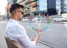 Man with smartphone and zodiac signs in city. Technology, astrology, horoscope and people concept - close up of man with smartphone and leo zodiac sign in city royalty free stock photography