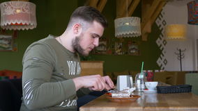 Man with smartwatch eating a dessert cake pie in the restaurant stock footage