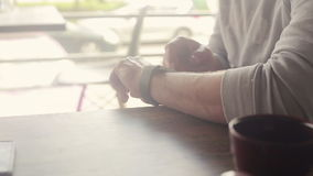 Man with smartwatch sitting in cafe in city stock footage