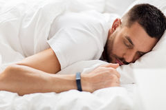 Man with smartwatch sleeping in bed Stock Image