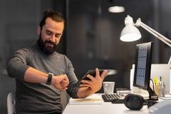 Man with smartwatch and tablet pc at night office Royalty Free Stock Photo