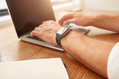 Man with a smartwatch working on laptop Royalty Free Stock Image