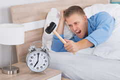 Man Smashing Alarm Clock With Hammer Stock Image