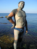 Man, smeared by mud at sea. Man was smeared by useful therapeutic mud on the shore of Azov sea in order to obtain therapeutic effect. Mud gradually dries in the Royalty Free Stock Image