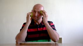 A man smears his face with an apple for skin rejuvenation. Mask of apples for the face. means for removing wrinkles stock footage